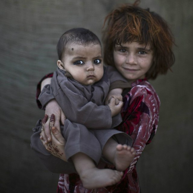 Khalzarin Zirgul, 6, holds her cousin, Zaman, 3 months, as they pose for a picture while playing with other children in a slum on the outskirts of Islamabad, Pakistan